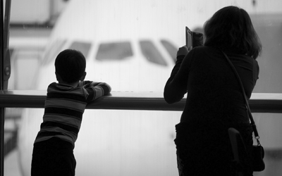 Woman and child watching plane at gate in airport